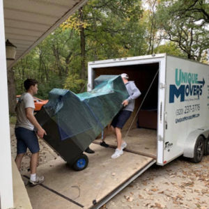 Two team members moving a large item into a truck