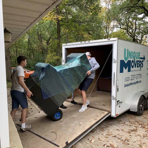 Unique Movers team wrapped and moving an arcade machine.