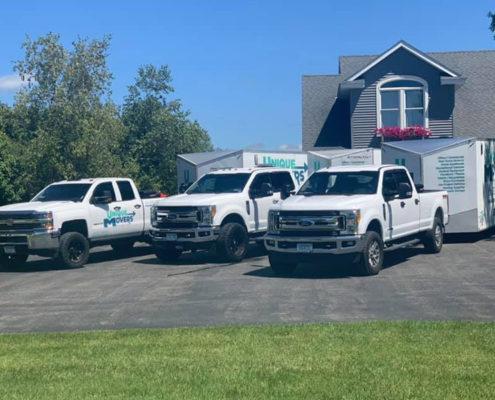 Trio of Unique Movers trucks and trailers preparing for a move