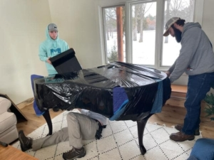 Unique Movers team padding and wrapping a piano move in Little Falls, MN to Park Rapids, MN.
